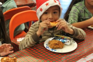 small boy wearing Santa hat, enjoying breakfast